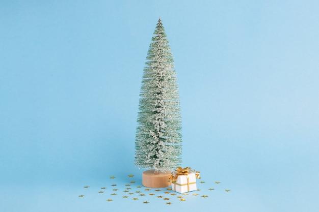 Albero di natale nevoso e regalo su sfondo blu pastello