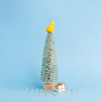 Albero di natale nevoso in protezione invernale e regalo su sfondo blu pastello