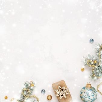 Sfondo bianco neve di natale, regalo, ramoscelli e decorazioni blu oro.