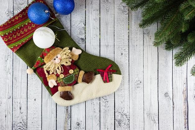 Calza di natale con uno gnomo, decorazioni natalizie su un tavolo di legno
