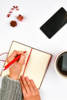 Spazio di natale da blocco note, telefono, tazza di caffè. tazza rossa in ceramica con caffè nero. layout di capodanno. vista dall'alto. una mano femminile scrive in un taccuino di vene.