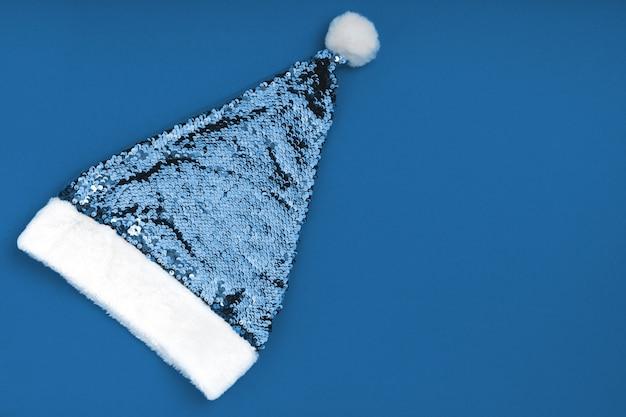 Cappello di babbo natale dorato scintillante di natale su sfondo blu. fondo di festa di natale natale capodanno.