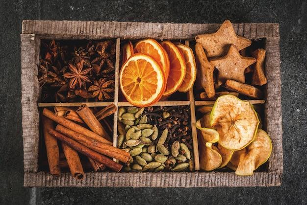 Spezie natalizie da forno, cocktail, vin brulè, con biscotti di panpepato (stelle) - mela secca, arancia, cardamomo, chiodi di garofano, cannella, anice. vecchia scatola di legno, tavolo di pietra nera. copia spazio vista dall'alto