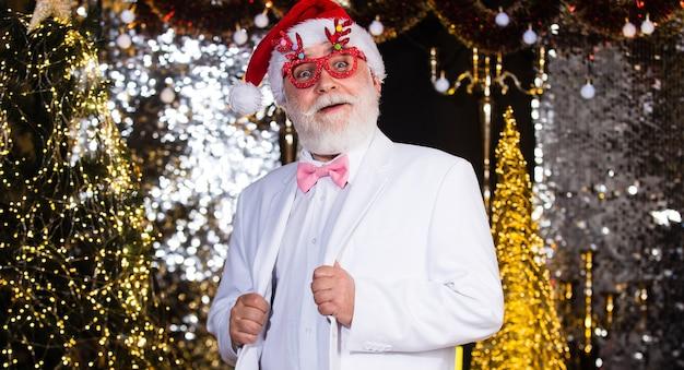 Spirito natalizio. celebrazione allegra. decorazione natalizia. babbo natale. uomo anziano con la barba bianca. l'uomo barbuto del nonno celebra il natale elegante nonno in tuta. festa aziendale.