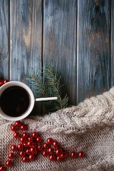 Spirito natalizio e festività natalizie. elementi di arredo su fondo in legno. maglione lavorato a maglia e cordoncino rosso con una tazza di caffè caldo.