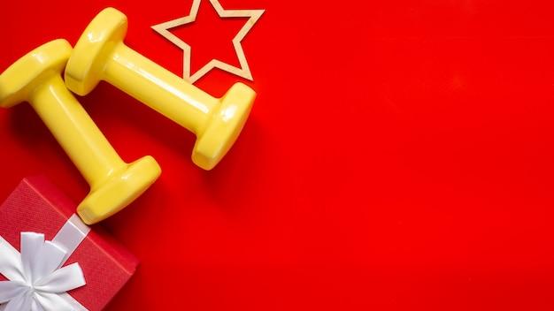 Composizione sportiva natalizia con manubri, statuetta in legno a stella, confezione regalo rossa con fiocco bianco su sfondo rosso.