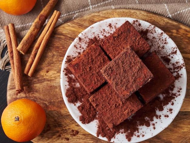Caramelle di soufflé fatte a mano quadrate piatte di laici di natale ancora di vita al cioccolato con bastoncini di cannella e arance