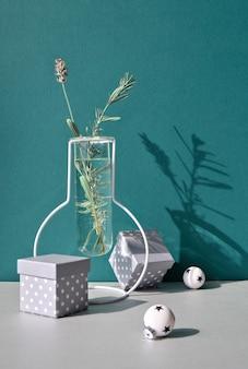 Natale ancora in vita, disposizione minima con fiori invernali in un moderno vaso di vetro e decorazioni natalizie bianche