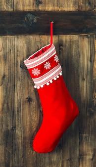 Calza di natale. calzino rosso che appende sopra fondo di legno rustico. decorazione delle feste