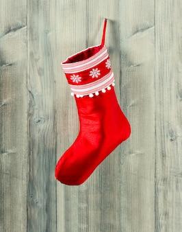 Calza di natale. calzino rosso con fiocchi di neve per i regali di babbo natale appesi su fondo rustico in legno