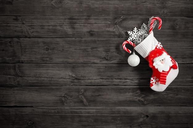 Calza di natale con doni che appendono sulla vecchia parete di legno scura