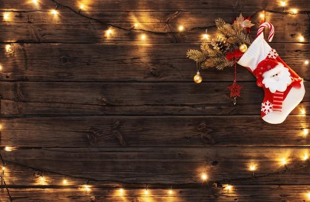 Calza di natale con doni che appendono sul vecchio legno scuro