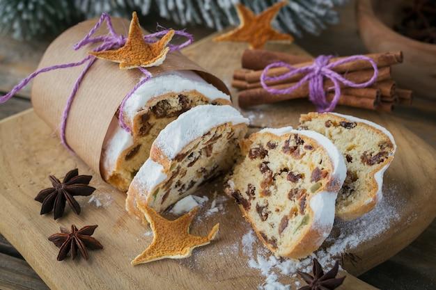 Christmas stollen affettato su una tavola di legno con stecca di cannella e anice stellato