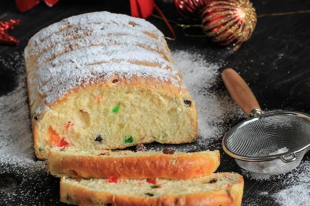Stollen di natale. pane dolce tradizionale alla frutta con zucchero a velo. decorazione per la tavola delle vacanze di natale, decorata con mini albero di natale e decorazioni.