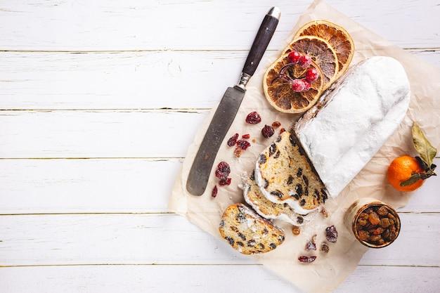 Stollen di natale tradizionale pagnotta di frutta dolce con zucchero a velo vacanze di natale messa in tavola vista dall'alto