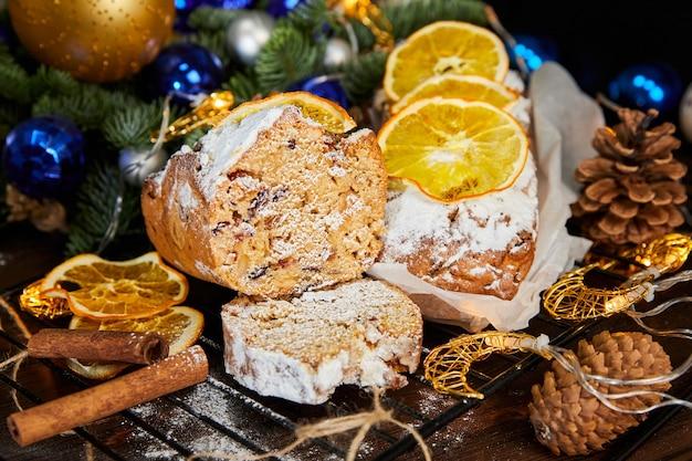 Stollen natalizio con spezie, uvetta, noci e frutta candita su uno sfondo di ghirlande luminose