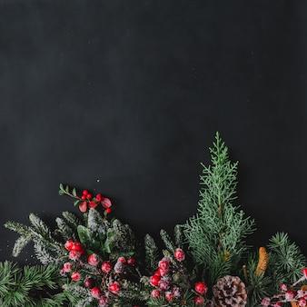 Superficie di natale fatta di cose invernali naturali sulla lavagna scura