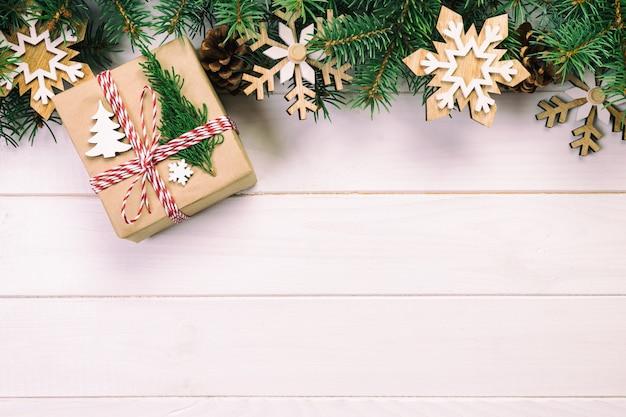 Il natale sorge con l'albero di abete e il contenitore di regalo sulla tavola di legno.