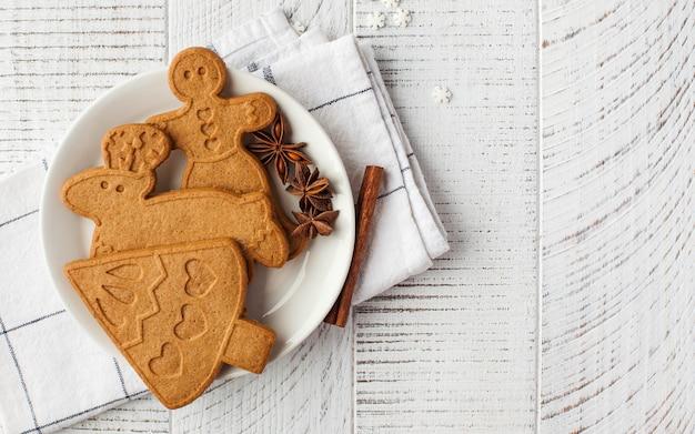 Superficie di natale con biscotti allo zenzero e spezie su una superficie in legno chiaro