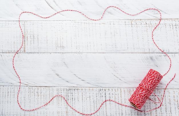 Superficie di natale con nastro rosso, giocattoli, scatole regalo e pigne sul vecchio tavolo di superficie in legno bianco. messa a fuoco selettiva.