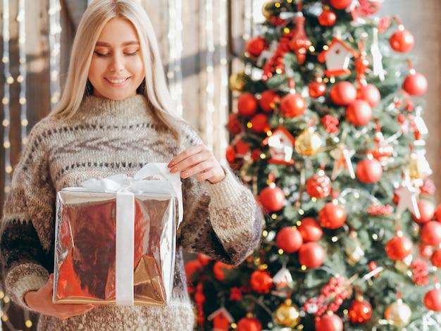 Sorpresa di natale. signora felice in maglione accogliente apertura grande confezione regalo lucida, sorridente. sfocatura abete decorato in