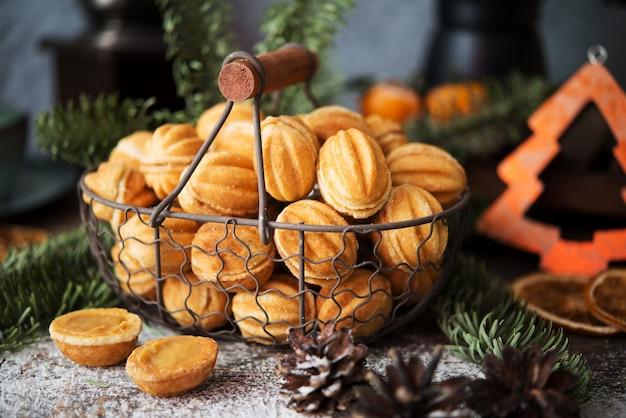 Dolci di natale biscotti noci con latte condensato sul tavolo festivo, decorazioni natalizie, messa a fuoco selettiva