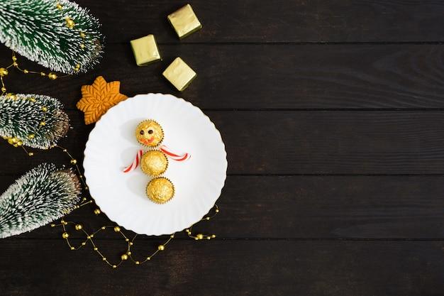 Decorazioni per la tavola di natale con pupazzo di neve di caramelle sul piatto con l'albero di natale