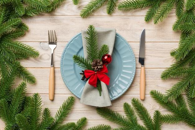 Tavola natalizia con decorazioni natalizie e piatti, kine, forchetta e cucchiaio. priorità bassa di festa di natale. vista dall'alto