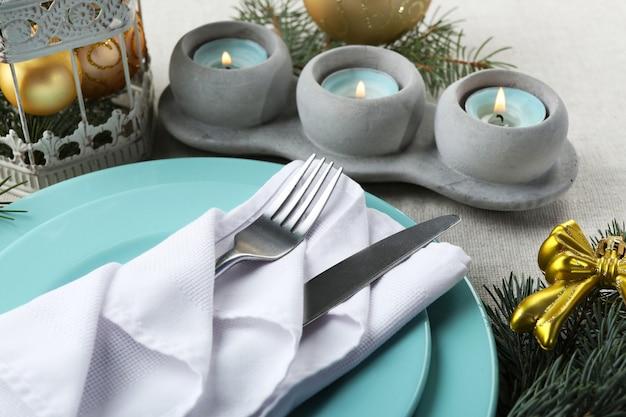 Regolazione della tavola di natale nei colori blu, dorati e bianchi su sfondo grigio tovaglia
