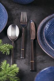 Regolazione della tavola di natale. decoro blu scuro con ramo di abete. piatti, bicchieri da vino e posate con tessuto decorativo su sfondo scuro.