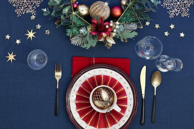 Tavola di natale nei colori oro, bordeaux e blu scuro. vista piana laico e dall'alto sul layout del tavolo da pranzo con posate dorate e decorazioni natalizie sulla tovaglia di lino blu scuro.