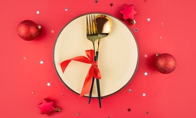 Regolazione della tavola di natale su uno sfondo rosso. decorazioni natalizie festive. sfondo di natale.