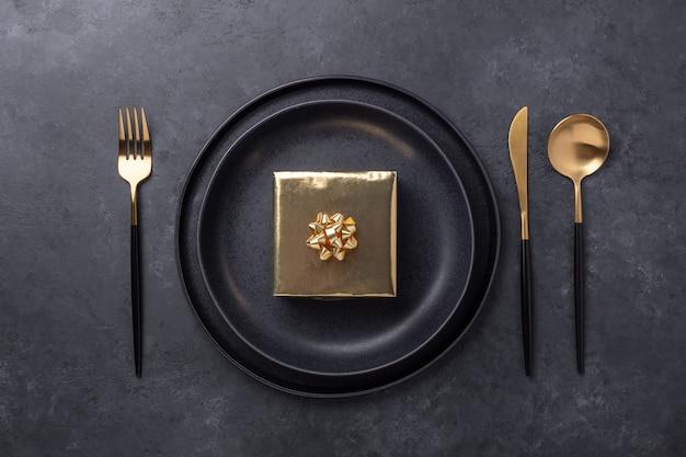 Impostazione della tavola di natale con piatto in ceramica nera e confezione regalo in oro su sfondo di pietra nera. vista dall'alto - immagine