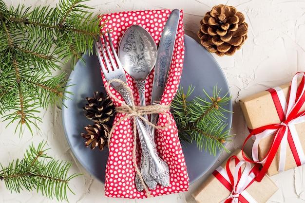 Regolazione della tavola di natale con bastoncino di zucchero, albero di natale, pigne e regalo, sulla tavola bianca, spazio della copia di vista superiore.