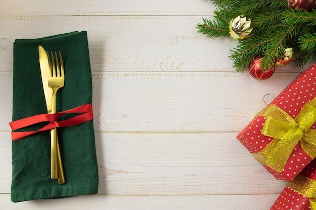 Regolazione della tavola di natale con regalo e posate su uno sfondo bianco