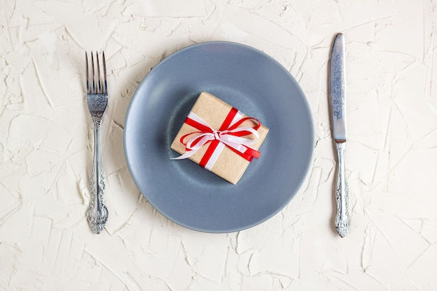 Tavola di natale con scatola regalo in lamiera grigia e argenteria