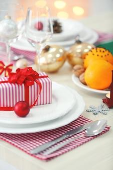 Impostazione della tavola di natale con decorazioni natalizie sullo sfondo del camino