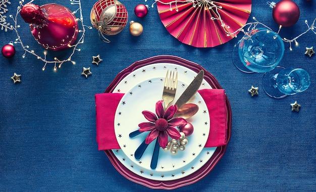 Allestimento tavola natalizia con piatto bianco, utensili dorati, tovagliolo rosso scuro e decorazioni dorate. vista piana laico e superiore su sfondo tessile di lino blu scuro. ghirlanda di luci natalizie.