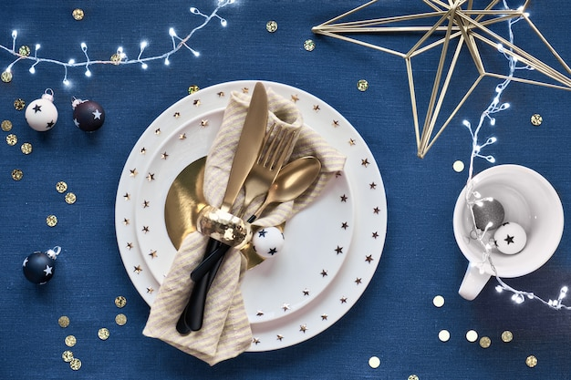 Tavola di natale allestita con piatto bianco e utensili dorati e decorazioni dorate. vista piatta, vista dall'alto sul classico blu. sfondo tessile di lino blu scuro.