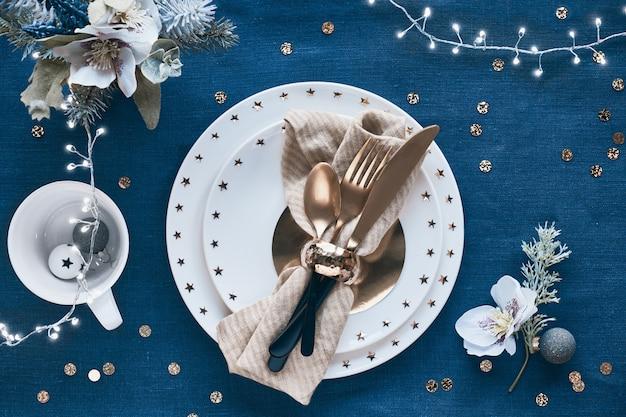 Tavola di natale allestita con piatto bianco e utensili dorati e decorazioni dorate. vista piana laico e superiore su sfondo blu classico lino tessile.