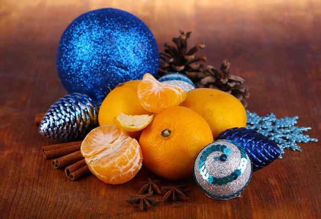 Mandarini di natale e giocattoli di natale sul primo piano della tavola di legno