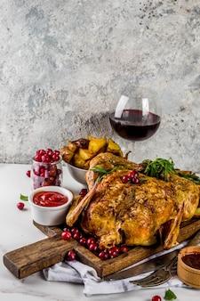 Natale, cibo del ringraziamento, pollo arrosto al forno con mirtilli rossi ed erbe, servito con verdure fritte, vino di bacche fresche e salse