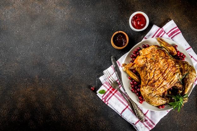 Natale, cibo del ringraziamento, pollo arrosto al forno con mirtilli rossi ed erbe aromatiche, servito con verdure fritte e salse sul tavolo arrugginito scuro, vista dall'alto