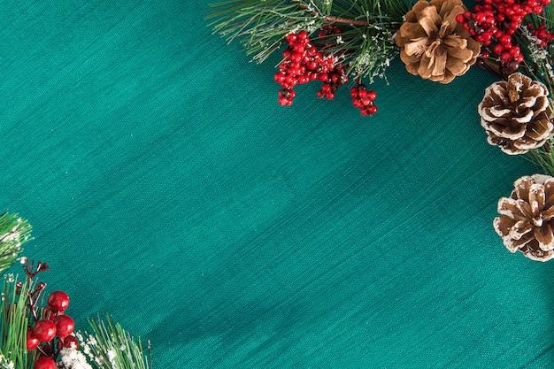 Tema natalizio. rami di pino con coni, bacche e neve al verde dipinto su tela di fondo.