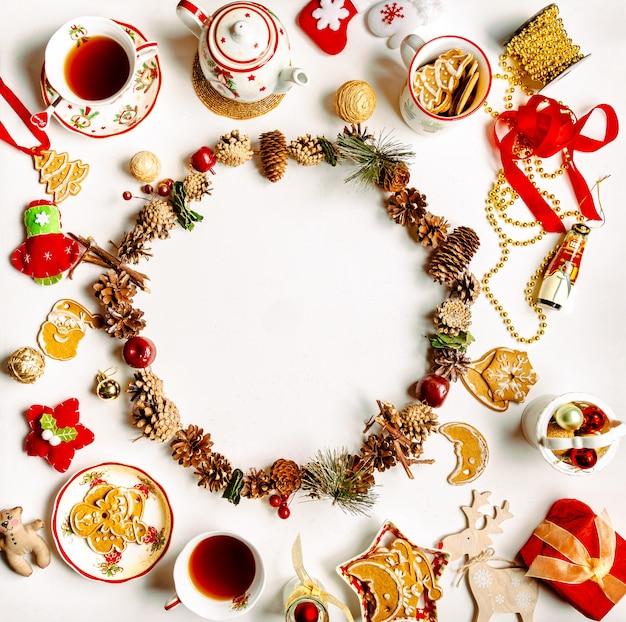 Flatlay a tema natalizio con tè, biscotti di panpepato, decorazioni, ghirlanda di pigne su sfondo bianco con spazio di copia