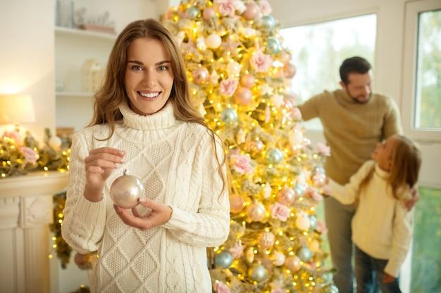 Periodo natalizio. famiglia felice sveglia che decora l'albero di natale e si sente bene