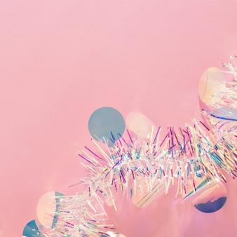 Ghirlanda e coriandoli di orpelli natalizi su sfondo rosa spazio copia.