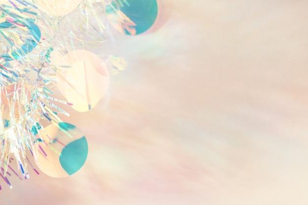 Cornice di ghirlande di natale tinsel su sfondo beige pastello con spazio di copia.