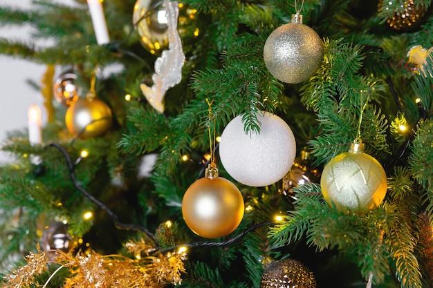 Palla di natale giocattolo appeso a un ramo di abete rosso. albero di capodanno decorato con una ghirlanda.