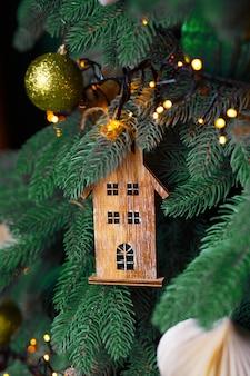 Giocattolo di natale su un albero di natale, casa in legno.